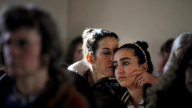 Elizabeth Bogdanoff, left, kisses her daughter Julia, 13, both of Newtown, Conn., during a prayer service at St John's Episcopal Church in Newtown, Saturday, Dec. 15, 2012. The massacre of 26 children and adults at Sandy Hook Elementary school elicited horror and soul-searching around the world even as it raised more basic questions about why the gunman, 20-year-old Adam Lanza, would have been driven to such a crime and how he chose his victims. (AP Photo/David Goldman)