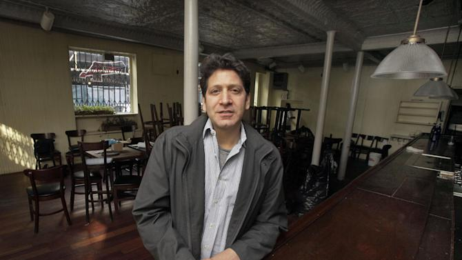 FILE - In this file photo of Dec. 4, 2012, photo, proprietor Adam Weprin, of the Bridge Cafe, in New York's South Street Seaport, poses for a photo at the restaurant's bar after his establishment was shuttered by Superstorm Sandy. Nearly four months after Superstomr Sandy hit, the historic cobblestone streets near the water's edge in lower Manhattan are eerily deserted, and among local business owners, there is a pervasive sense that their plight has been ignored by the rest of Manhattan.  (AP Photo/Richard Drew, File)