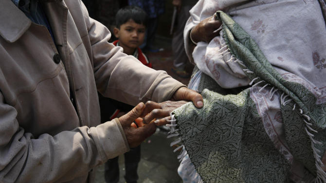 In this Sunday, Feb. 16, 2014 photo, an Indian man suffering from leprosy helps other leprosy affected woman at a leper colony in New Delhi, India. The stigma of leprosy endures in India, even though the country has made great strides against the disease, which is neither highly contagious nor fatal. Now the number of new annual cases has risen slightly after years of steady decline, and medical experts say the enormous fear surrounding leprosy is hindering efforts to finally eliminate it.(AP Photo/Manish Swarup)