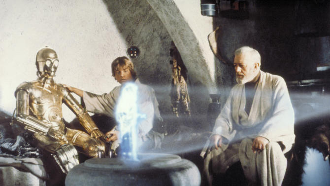 """** FOR ONE-TIME-USE-ONLY WITH MALCOLM RITTER'S STORY SLUGGED: VIDEO IN 3-D ** In this publicity image released by LucasFilm Ltd & TM, characters, from left, Anthony Daniels  portraying C-3PO, Mark Hamill portraying Luke Skywalker and Alec Guinness portraying Ben Obi-Wan Kenobi look at a hologram of Princess Leia, portrayed by Carrie Fisher in a scene from the original 1977 """"Star Wars"""" film. (AP Photo/Lucasfilm Ltd & TM) ** NO SALES, ARCHIVE OUT, MUST CONTACT LUCASFILM FOR ADDITIONAL USE **"""