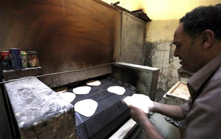 A worker puts dough into an oven to be baked in a bakery in Cairo March 12, 2013. REUTERS/Mohamed Abd El Ghany