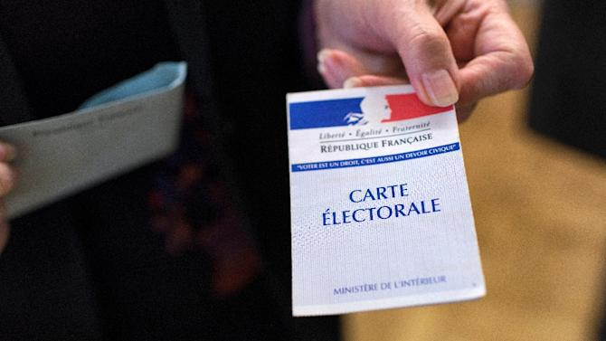 A woman presents her voting card during the first round of the regional elections in the Rhone-Alpes-Auvergne region on December 6, 2015 at a polling station in Limonest