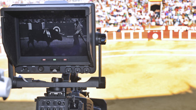 A TV camera films during a bullfight in Valladolid, Spain Wednesday Sept. 5, 2012. Bullfights returned live to Spanish state TV Wednesday evening, six years after the fights were banned from the widely watched public channel  with the broadcast featuring one of Spain's most storied bullfighters and giving a boost to a tradition hit hard by declining popularity and a dire economic crisis. The RTVE broadcast from the northern city of Valladolid is a big victory for pro-bullfighting forces that saw bullfighting banned altogether this year in the northeastern region of Catalonia; it's a defeat for animal rights activists who denounce bullfighting as barbaric. The transmissions were halted in 2006 by Spain's previous Socialist administration, which said they were costly and coincided with key TV viewing hours for young children. (AP Photo/Israel L.  Murillo)