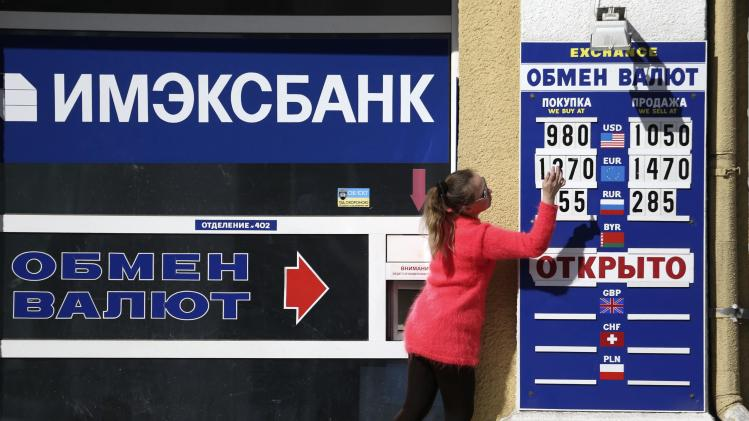 An employee changes rates on a notice board at a currency exchange in Simferopol
