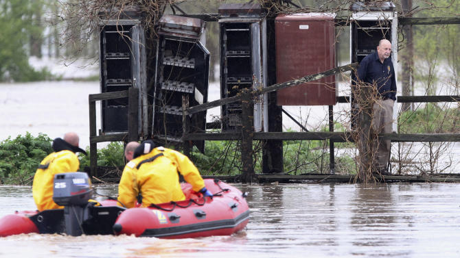 Smithton, Ill., firefighters Capt. Robert Lindauer and Cory Ellis use a boat to rescue Dan Bauer of Venedy, Ill., after Bauer's vehicle was engulfed in water as he was stopped by high water on Route 158 in Mascoutah, Ill., Thursday, April 18, 2013. Bauer was able to get to a dry area where he waited about an hour for crews to rescue him. (AP Photo/Belleville News-Democrat, Derik Holtmann)