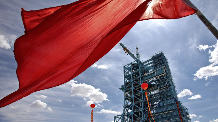 In this Friday, June 8, 2012 photo, a flag flies near a rocket launch pad at the Jiuquan launch center in Jiuquan, China's northwest Gansu province. China will launch three astronauts this month to dock with an orbiting experimental module, and the crew might include its first female space traveler, a government news agency said Saturday. (AP Photo) CHINA OUT