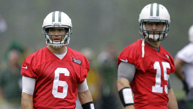 New York Jets quarterbacks Mark Sanchez, left, and Tim Tebow look on during NFL football practice, Thursday, May 24, 2012, in Florham Park, N.J. (AP Photo/Julio Cortez)