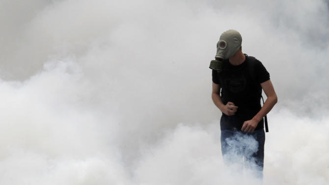 A protester walks among tear gas thrown by riot policeduring clashes in central Athens Wednesday, June 29, 2011.Greek deputies are to vote Wednesday on a deeply unpopular austerity bill that has provoked days of rioting in the streets of Athens, with the result of the vote determining is Greece can avoid a potentially disastrous financial default in the coming weeks .(AP Photo/Petros Giannakouris)
