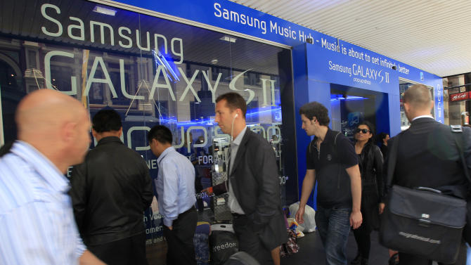 FILE - In this Oct. 13, 2011 file photo, people walk by a Samsung store in Sydney. Samsung Electronics Co. is closer to selling its new Galaxy tablet computer in Australia after a court on Wednesday, Nov. 30, overturned a ruling that favored Apple's allegations Samsung had copied its iPad and iPhone. (AP Photo/Rick Rycroft, File)
