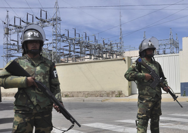 Military police stand guard outside Transportadora de Electricidad, the Spanish electricity grid's Bolivian subsidiary, in Cochabamba, Bolivia, Tuesday, May 1, 2012. Bolivia's President Evo Morales says his government is completing the nationalization of the country's electricity industry by taking over its electrical grid from the Spanish-owned company, Red Electrica. (AP Photo)