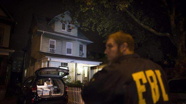 An FBI agent stands guard as evidence sits in the trunk of a vehicle at the Brooklyn residence of Rabbi Mendel Epstein during an investigation, early Thursday, Oct. 10, 2013, in New York. Several defendants, including Epstein and another rabbi, were arrested in an overnight sting in New York and New Jersey and accused by the FBI of plotting to kidnap and beat a man to force him to grant a religious divorce. (AP Photo/John Minchillo)