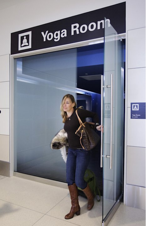 In this Friday, Jan. 27, 2012 photo, traveler Maria Poole leaves San Francisco International Airport's new Yoga Room, in San Francisco. The quiet, dimly lit studio officially opened last week in a for