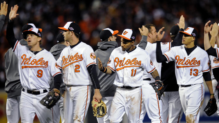Baltimore Orioles' Nate McLouth, from left, J.J. Hardy, Robert Andino and Manny Machado high-five teammates after Game 2 of the American League division baseball series against the New York Yankees on Monday, Oct. 8, 2012, in Baltimore. Baltimore won 3-2. (AP Photo/Nick Wass)