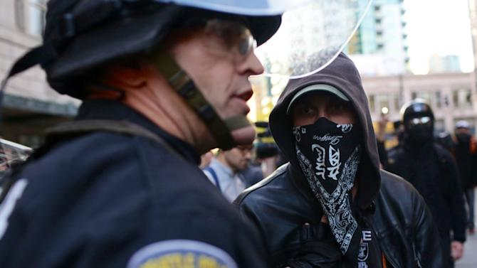 """A police officer pushes back a black-masked demonstrator during a May Day protest in Seattle Wednesday, May 1, 2013. Police used """"flash bangs"""" and pepper spray against some protesters who pelted them with rocks and bottles late Wednesday, as violence erupted during May Day in Seattle. Several dozen protesters, many using bandanas to cover their faces, began clashing with police in downtown Seattle hours after a peaceful immigrant-rights march ended. (AP Photo/Jordan Stead, seattlepi.com)"""