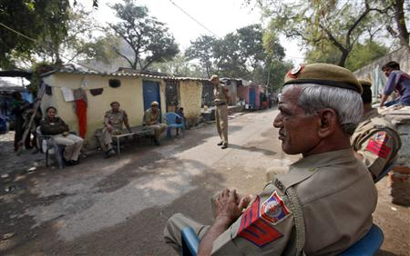 Police sit inside the Ravi Das camp, the slum where four of the six accused in a rape case including Ram Singh reside, in New Delhi