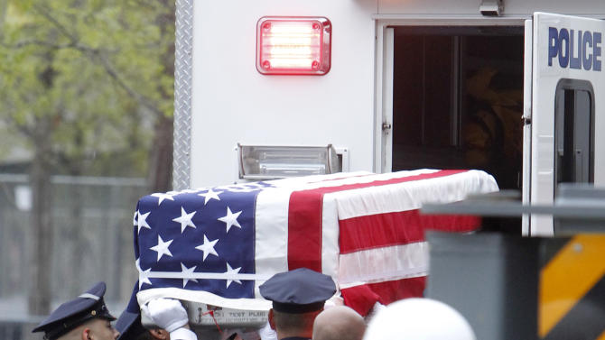 A flag-draped casket is lifted out of a police vehicle during the ceremonial transfer of unidentified remains of those killed at the World Trade Center from the Office of the Chief Medical Examiner to the World Trade Center site, Saturday, May 10, 2014, in New York. The remains will be transferred to an underground repository in the same building as the National September 11 Memorial Museum. (AP Photo/Jason DeCrow)