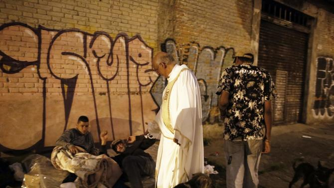 Priest Lancellotti talks with homeless people on the street as he invites them to a free Christmas dinner at Sao Miguel Arcanjo church in Sao Paulo