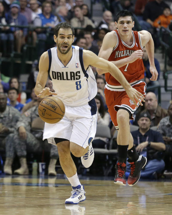 Dallas Mavericks point guard Jose Calderon (8), of Spain, drives up court as Milwaukee Bucks forward Ersan Ilyasova (7), of Turkey, give chase during the second half of an NBA basketball game Saturday