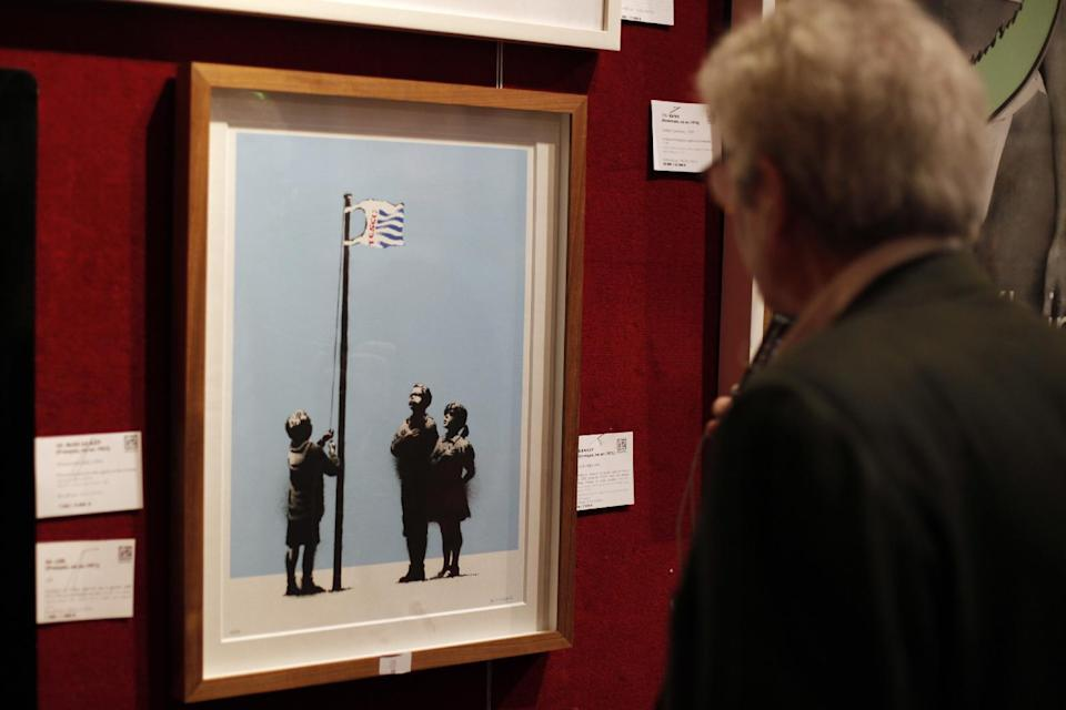 "A visitor looks ""Very Little Helps"" by British artist Banksy, exhibited at Drouot auction house, in Paris, Thursday Oct.24, 2013. The sculpture is one among dozens of art pieces from street artists which will be auctioned Friday Oct. 25. (AP Photo/Thibault Camus)"
