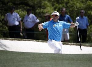 Britain's Lee Westwood climbs from the sand trap after a shot on the first hole during the third round of the Masters golf tournament at the Augusta National Golf Club in Augusta