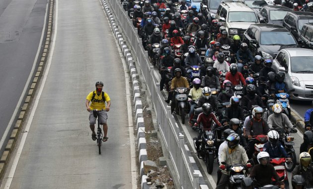 File photo of man riding a bicycle in a bus lane next to a morning rush hour traffic jam in Jakarta