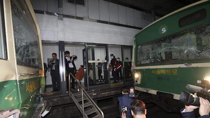 Windows of two subway trains remain broken after their collision at Sangwangshipri subway station in Seoul, South Korea, Friday, May. 2, 2014. A subway train plowed into another train stopped at the station Friday, causing minor injuries for scores of people, a city official said. (AP Photo/Yonhap, Park Dong-ju) KOREA OUT