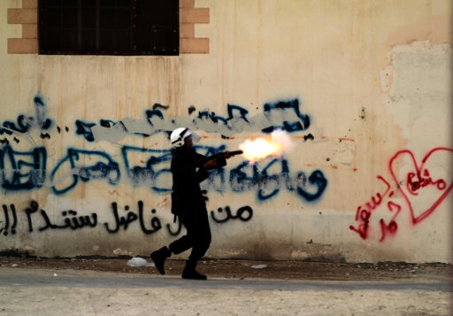 "A riot policeman fires a tear gas canister while chasing anti-government protesters Thursday, June 21, 2012, in Diraz, Bahrain. Riot police used tear gas and stun grenades to disperse a demonstration against alleged deaths of infants and miscarriages blamed on excessive tear gas. Graffiti on the wall reads, ""down Hamad,"" referring to Bahrain's king, ""you will regret killing Fadhel,"" referring to a village youth killed in earlier clashes, and, inside the heart, ""Mushaima,"" referring to a jailed opposition leader. (AP Photo/Hasan Jamali)"