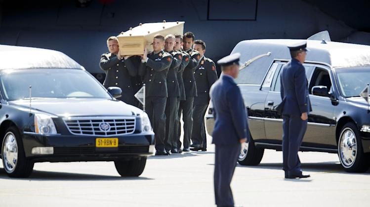 Pallbearers carry a coffin towards a hearse during a ceremony to mark the return of the first bodies, of passengers and crew killed in the downing of Malaysia Airlines Flight 17, from Ukraine at Eindhoven military air base, Netherlands, Wednesday, July 23, 2014. After being removed from the planes, the bodies are to be taken in a convoy of hearses to a military barracks in the central city of Hilversum, where forensic experts will begin the painstaking task of identifying the bodies and returning them to their loved ones. (AP Photo/Phil Nijhuis)