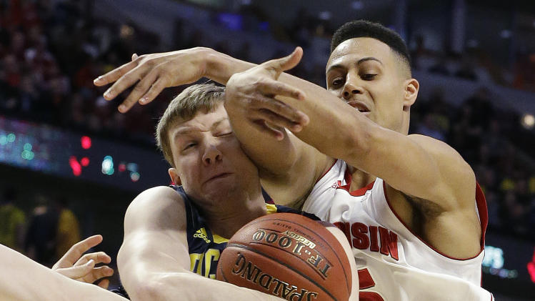 Michigan's Matt Vogrich grabs a rebound in front of Wisconsin's Ryan Evans (5) during the first half of an NCAA college basketball game at the Big Ten tournament Friday, March 15, 2013, in Chicago. (AP Photo/Nam Y. Huh)
