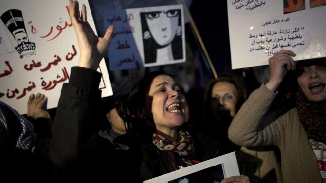 """Egyptian woman activists chant slogans while taking part in a protest  against sexual harassment and against the Islamist dominated Shura Council blaming women for the attacks against them, in Cairo, Egypt, Tuesday, Feb. 12, 2013. Arabic in the background reads """"The revolution will go through the bodies of women not over them."""" (AP Photo/Nasser Nasser)"""