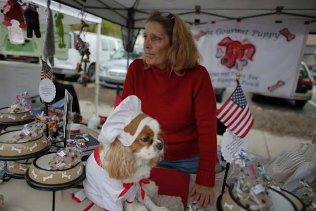 Cynthia Kopp and her dog Aires wait for customers at a farmers market, Saturday Oct. 6, 2012, in Doylestown Pa. Kopp, 56, lost her accounting job in the recession and now works part-time as a supermarket cashier and comes to the farmers market each week to sell $5 bags of her gourmet dog biscuits. &quot;If Aries could vote he would vote for Romney,&quot; Kopp said. &quot;Because mommy needs a job and she thinks Romney is the only candidate that could help get her one.&quot;(AP Photo/ Joseph Kaczmarek)