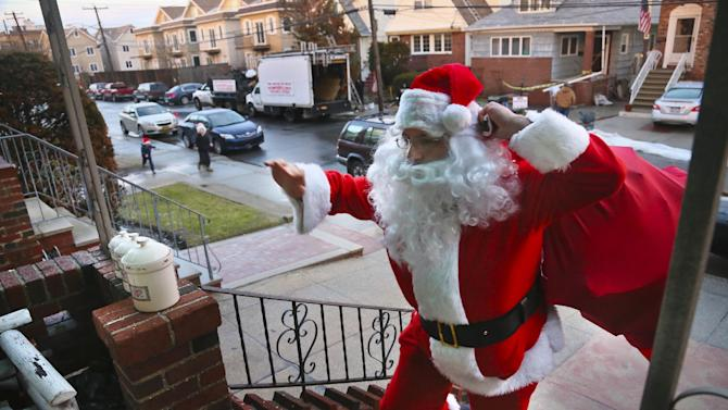 In this Tuesday, Dec. 18, 2012 photo, Michael Sciaraffo, as Santa Claus, arrives at the home of the Creamer family to deliver toys  in the Belle Harbor neighborhood of the Queens borough of New York. Using Facebook, Sciaraffo started a charitable enterprise to collect and personally deliver toys to children affected by superstorm Sandy, dressed as Santa Claus.  (AP Photo/Bebeto Matthews)