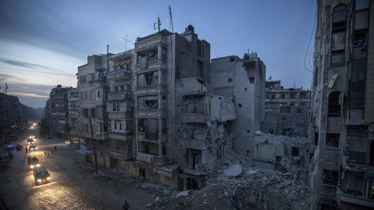 In this Thursday, Nov. 29, 2012 photo, night falls on a Syrian rebel-controlled area as destroyed buildings, including Dar Al-Shifa hospital, are seen on Sa'ar street after airstrikes  targeted the area last week, killing dozens in Aleppo, Syria. (AP Photo/Narciso Contreras)