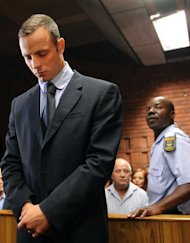 FILE - In this Friday Feb. 22, 2013 file photo Olympic athlete, Oscar Pistorius, is watched by a policeman while in the dock during his bail hearing in Pretoria, South Africa, charged with the shooting death of his girlfriend, Reeva Steenkamp. During the hearing last week it was heard how police stumbled and fumbled through the bail hearing and how investigator, Hilton Botha, possibly contaminated the crime scene and faced attempted murder charges himself. (AP Photo, File)
