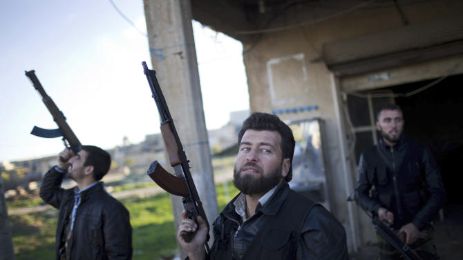 Free Syrian Army fighters look at a Syrian Army jet, not pictured, in Fafeen village, north of Aleppo province, Syria, Tuesday, Dec. 11, 2012. Syrian rebels including Islamic extremists took full control of a sprawling military base Tuesday after a bloody two-day battle that killed dozens of soldiers, activists said. It was the latest gain by opposition forces bolstered by an al-Qaida-linked group that has provided skilled fighters but raised concerns in the West.  (AP Photo/Manu Brabo)