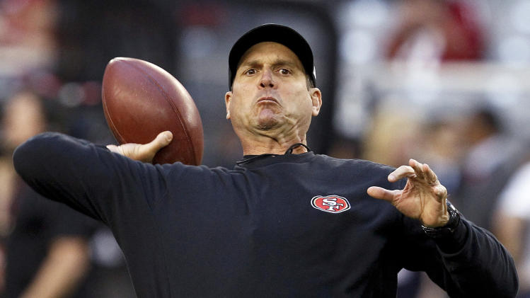 San Francisco 49ers head coach Jim Harbaugh throws a pass as the team warms up prior to an NFL football game against the Arizona Cardinals, Monday, Oct. 29, 2012, in Glendale, Ariz. (AP Photo/Ross D. Franklin)