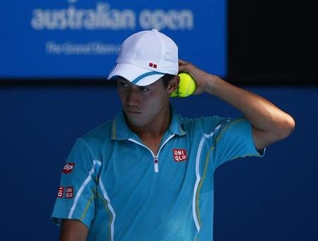 Kei Nishikori of Japan holds a ball during his men's singles match against David Ferrer of Spain at the Australian Open tennis tournament in Melbourne