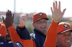 Houston Astros special instructor Roger Clemens, center, gives a high-five to players as they pass during a spring training baseball workout Monday, Feb. 18, 2013, in Kissimmee, Fla. His appearance comes at the time of the apparent suicide of former country star Mindy McCready. In 2008, she claimed a longtime relationship with Clemens. (AP Photo/David J. Phillip)