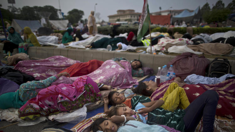 AP10ThingsToSee- Pakistani children and female protestors sleep in front of the parliament building, during weeklong protests from the eastern city of Lahore to the gates of parliament calling for Prime Minister Nawaz Sharif's ouster over alleged voting fraud, in Islamabad, Pakistan, Friday, Aug. 22, 2014. (AP Photo/Muhammed Muheisen)