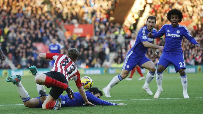 Fabregas of Chelsea is brought down by a challenge from Targett of Southampton in the penalty area during their English Premier League soccer match at St Mary's Stadium in Southampton, southern England