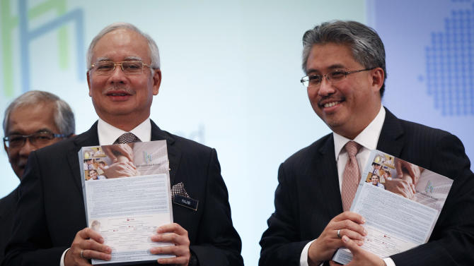 Malaysia's Prime Minister Najib Razak, left, holds the initial prospectus with Khazanah Nasional Managing Director Azman Mokhtar during the IHH Healthcare prospectus launch in Kuala Lumpur, July 3, 2012. IHH Healthcare, Asia's top hospital operator, said Tuesday it plans to raise 6.4 billion ringgit ($2 billion) from an initial public offering in Malaysia and Singapore. (AP Photo/Vincent Thian)