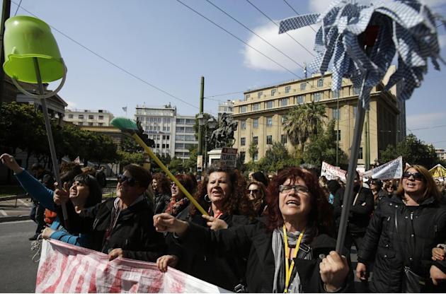 Protesting cleaning staff fired by the Finance Ministry marched holding up buckets and mops during a rally in Athens on Wednesday, March 12, 2014. A 24-hour strike by civil servants disrupted public s