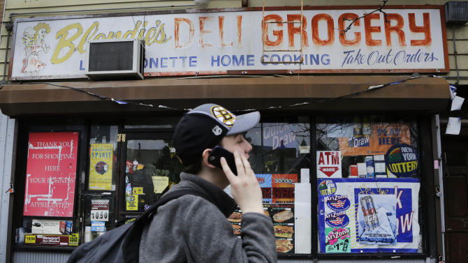 A teenager walks past Blondie's Deli and Grocery in New York, Monday, March 18, 2013. A new anti-smoking proposal would make New York the first city in the nation to keep tobacco products out of sight in retail stores. Mayor Michael Bloomberg says the goal is to reduce the youth smoking rate. The legislation would require stores to keep tobacco products in cabinets, drawers, under the counter, behind a curtain or in another concealed spot. They could only be visible when an adult is making a purchase or during restocking. (AP Photo/Mark Lennihan)