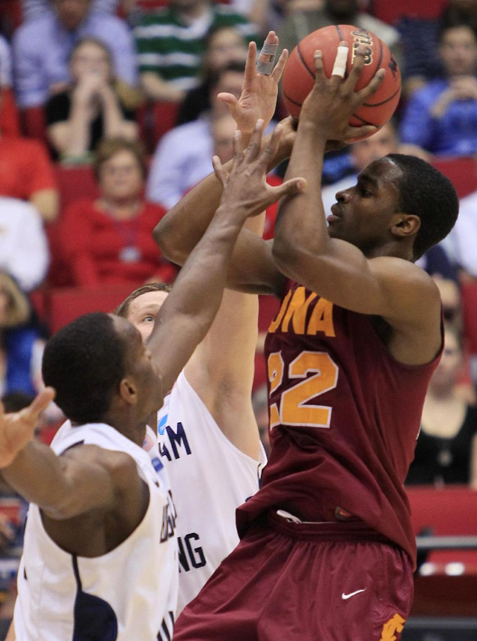 Iona guard Sean Armand (22) shoots against Brigham Young defenders in the first half of an NCAA men's college basketball tournament opening-round game, Tuesday, March 13, 2012, in Dayton, Ohio. (AP Photo/Al Behrman)