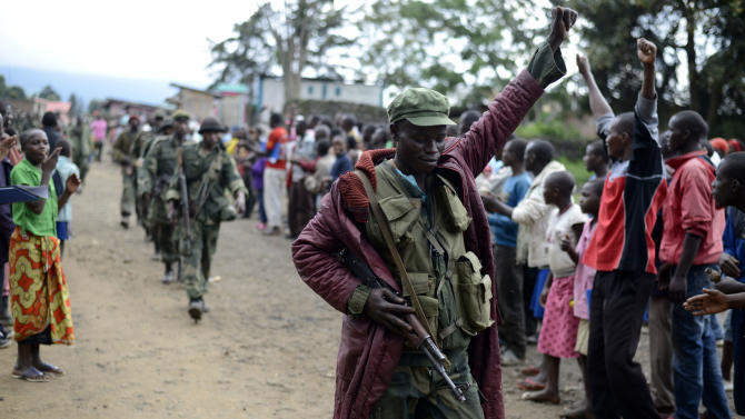 A Congolese army soldier responds to cheers from civilians as the army enters the town of Bunagana, eastern Congo, near the border with Uganda, Wednesday, Oct. 30, 2013. The Congolese army retook one of the last remaining strongholds of the M23 rebels Wednesday, with fighters heading for the hills as the military sought to extinguish the 18-month insurrection, officials said. As the army recaptured the town of Bunagana, leaving the M23 with a small sliver of territory, the civilian head of their movement crossed the border into Uganda prompting calls for his immediate extradition.(AP Photo/Joseph Kay)