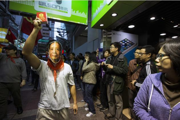 "A protester wearing a mask of late Chinese Communist Party leader Mao gestures with a ""Quotations from Chairman Mao Tse-tung"" book as mainland Chinese tourists pass by, during a anti-mainlan"