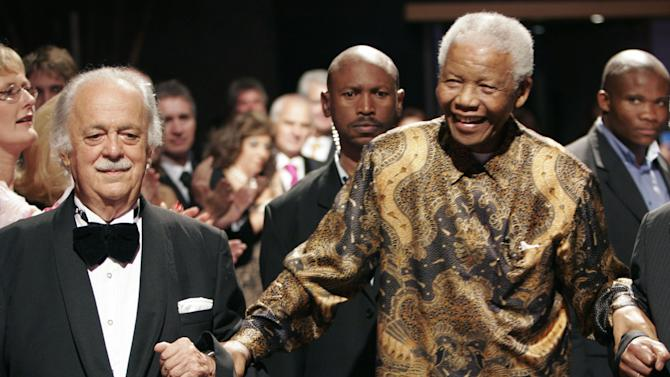 "FILE- In this file photo dated Wednesday Nov. 12, 2008, George Bizos, left, arrives for his 80th birthday party with former South African president Nelson Mandela, in Johannesburg. The 85-year old legal warhorse has tousled white hair, a soft, sometimes quavering voice, describes himself as ""computer-illiterate"" and sprinkles remarks with references to the ancient Greeks, is an executor of Mandela's will, and it is revealed Saturday March 8, 2014, that he refuses to retire from his human rights work. (AP Photo/Denis Farrell, FILE)"