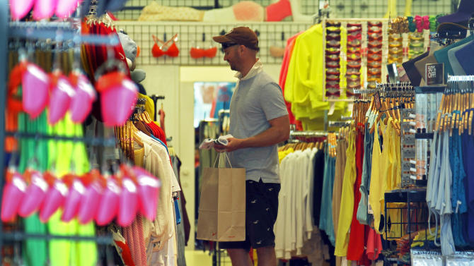 FILE- In this  Tuesday, April 24, 2012, file photo, a man views merchandise at an American Apparel store on the Third Street Promenade in Santa Monica, Calif. Consumer spending edged up modestly in April but personal income growth was the slowest in five months, raising concerns about the ability of Americans to keep spending in the future.  (AP Photo/Reed Saxon, file)