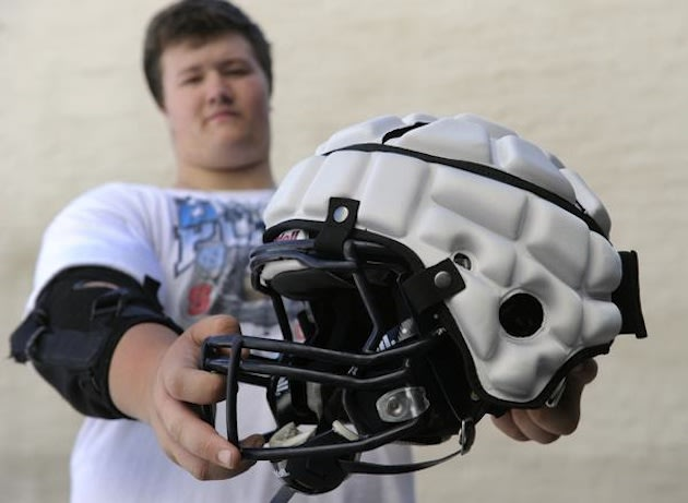 A Columbine freshman shows a Guardian Cap atop his helmet, which will be illegal in Colorado games — Denver Post