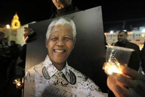 Palestinians light candles and hold placards bearing images of former South African President Nelson Mandela outside the Church of Nativity in the West Bank town of Bethlehem